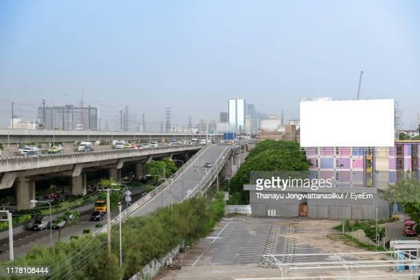 road amidst buildings in city against clear sky - billboard highway stock pictures, royalty-free photos & images