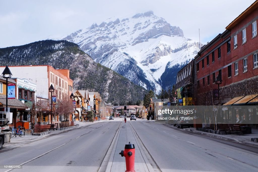 Road Amidst Buildings In City Against Sky During Winter : Stock Photo