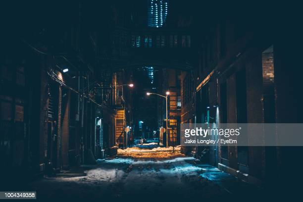 road amidst buildings in city at night during winter - alley stock photos and pictures