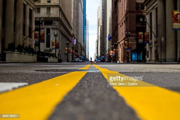 road amidst buildings in city - double yellow line stock photos and pictures