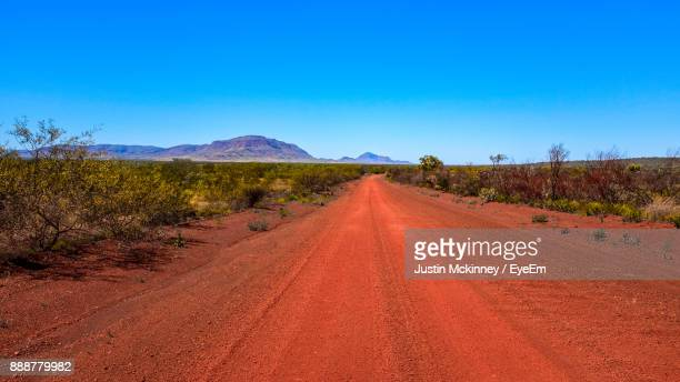 road amidst desert against clear blue sky - austrália - fotografias e filmes do acervo
