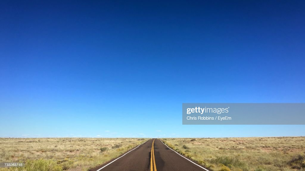 Road Amidst Field Against Clear Blue Sky : Stock Photo