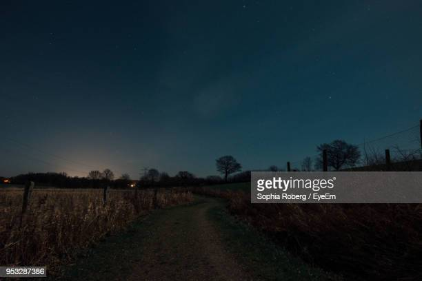 Road Amidst Field Against Clear Sky At Night
