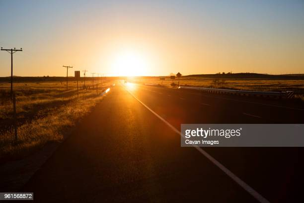 road amidst field against clear sky during sunset - texas stock photos and pictures
