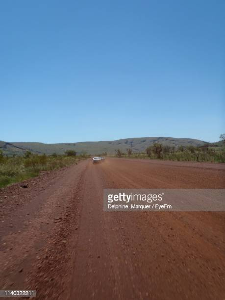 road amidst field against clear sky - marquer stock pictures, royalty-free photos & images