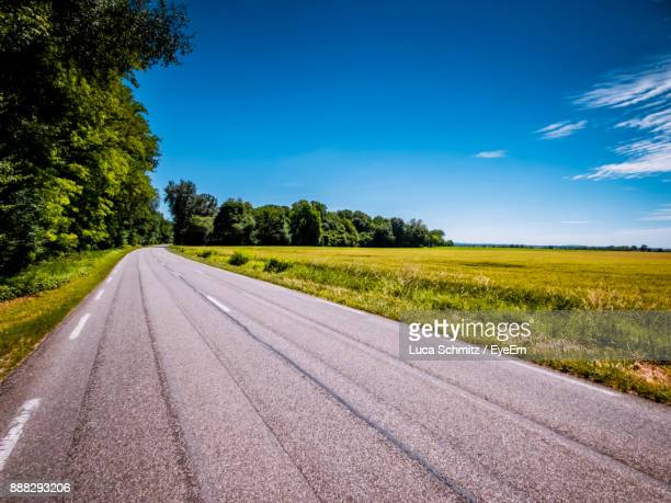 road amidst field against clear sky - country road stock pictures, royalty-free photos & images