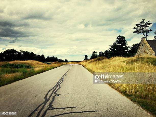 Road Amidst Field Against Cloudy Sky