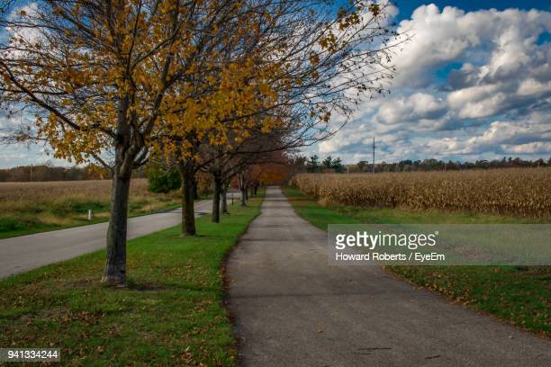 road amidst field against sky during autumn - norristown stock pictures, royalty-free photos & images