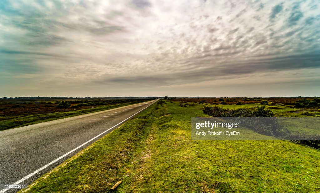 Road Amidst Field Against Sky : Stock Photo