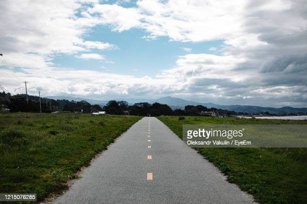 road amidst field against sky - oleksandr vakulin stock pictures, royalty-free photos & images