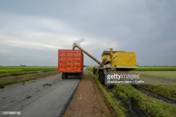 road amidst field against sky - shaifulzamri stock pictures, royalty-free photos & images