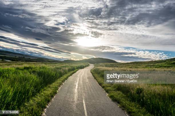 road amidst field against sky - wide stock pictures, royalty-free photos & images
