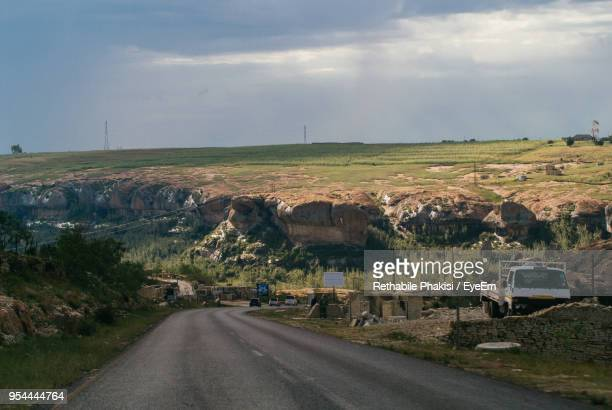 road amidst field against sky - lesotho stock photos and pictures