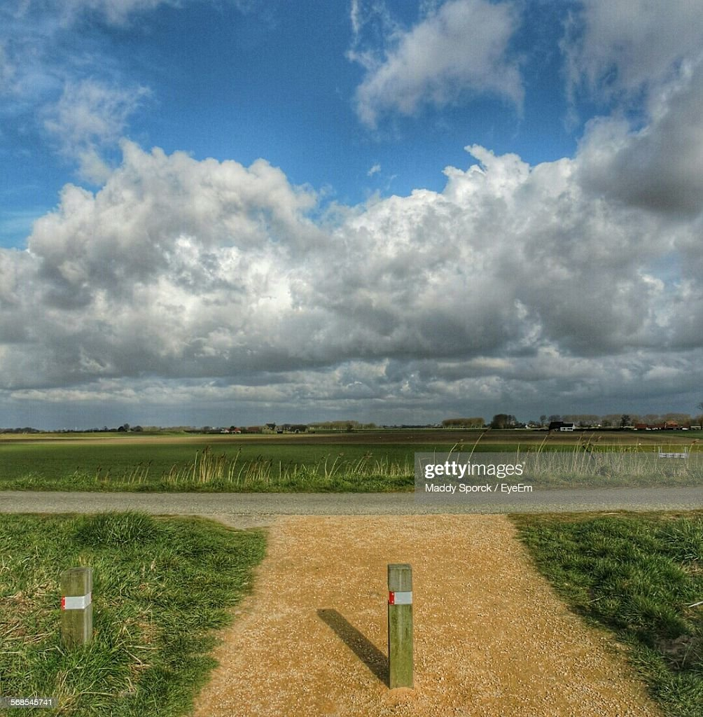 Road Amidst Grassy Field Against Cloudy Sky : Stock Photo