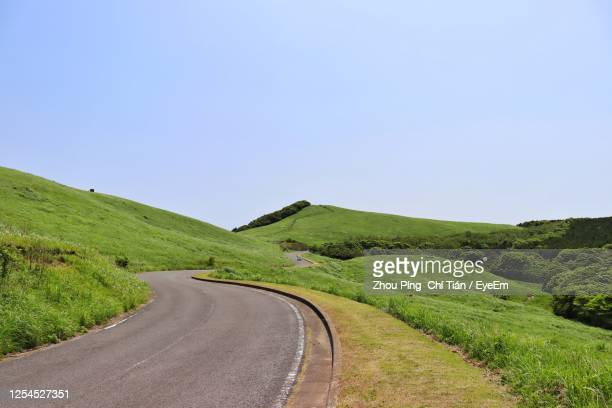 road amidst green landscape against clear sky - 台地 ストックフォトと画像