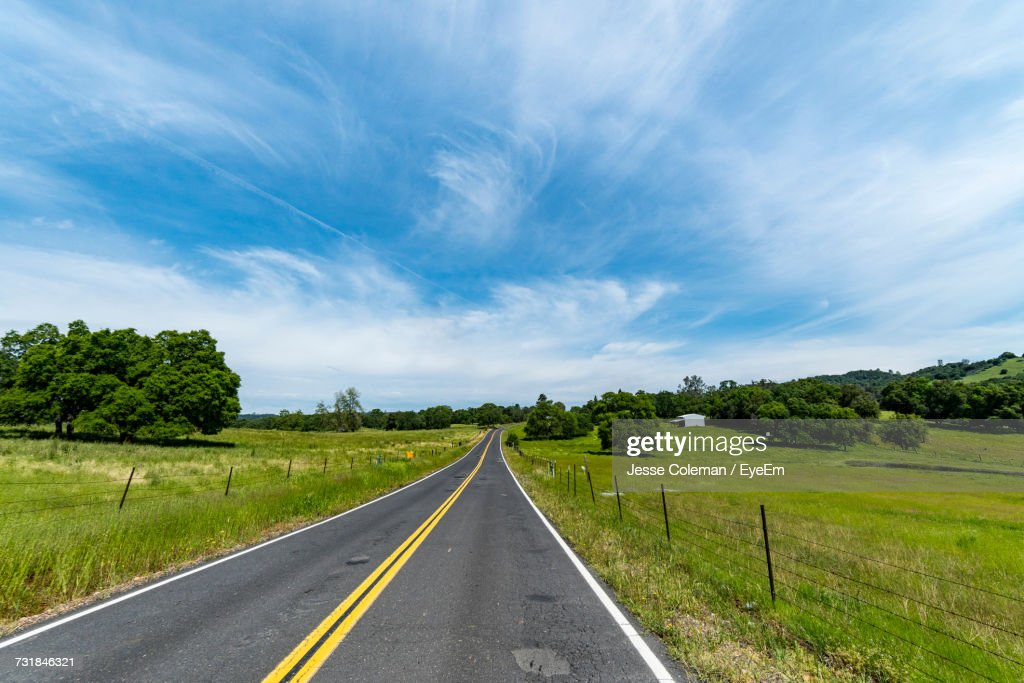 Road Amidst Green Landscape Against Sky : Stock Photo