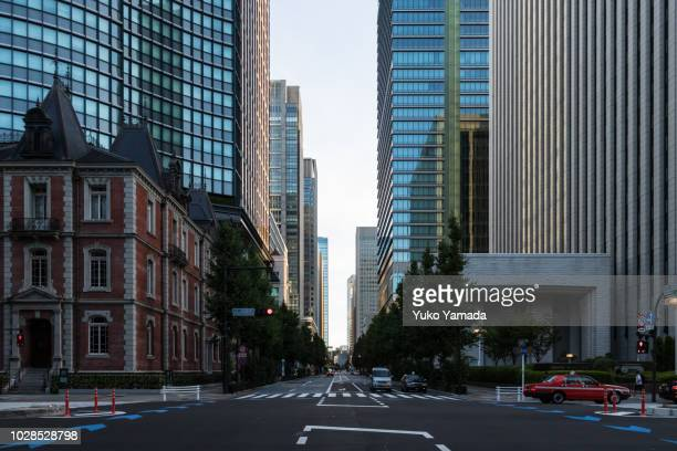 road amidst high-rise building during  morning - オフィス街 ストックフォトと画像