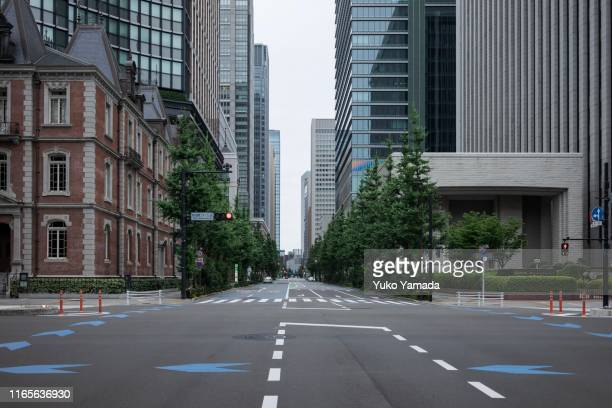 road amidst high-rise building during morning - 丸の内 ストックフォトと画像