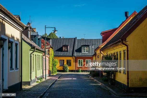 road amidst houses against sky - lund stock photos and pictures