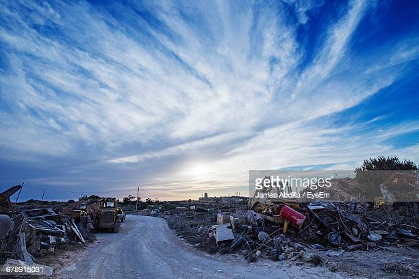 Road Amidst Junkyard Against Sky During Sunset