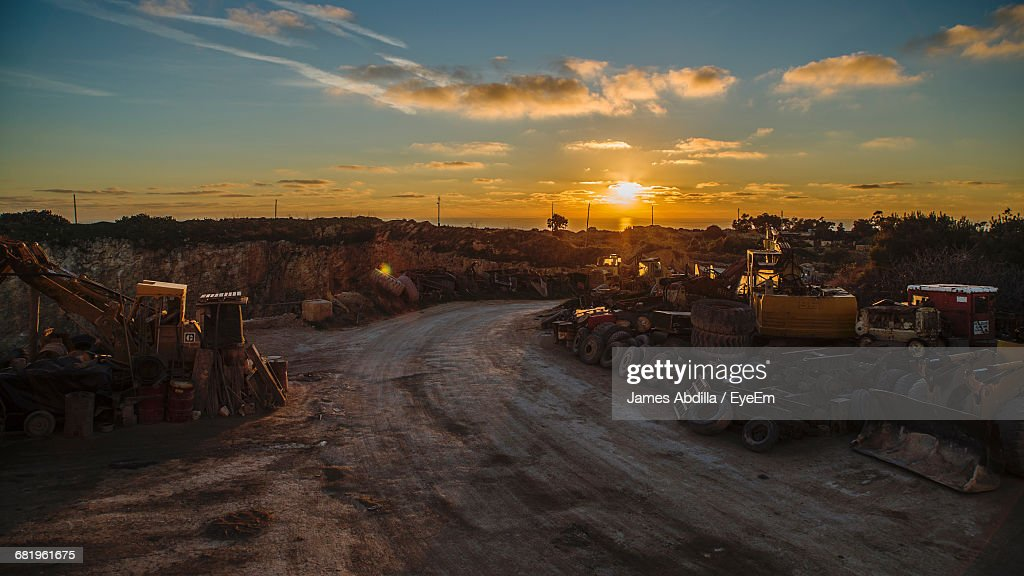 Road Amidst Junkyard Against Sky During Sunset : Stock Photo