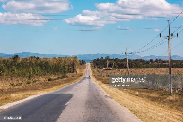 road amidst land against sky - bortes stock-fotos und bilder