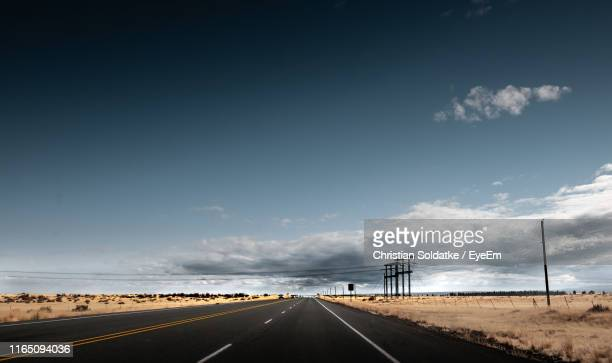 road amidst landscape against sky - christian soldatke stock pictures, royalty-free photos & images