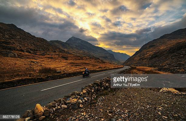 road amidst mountains against dramatic sky - snowdonia stock photos and pictures