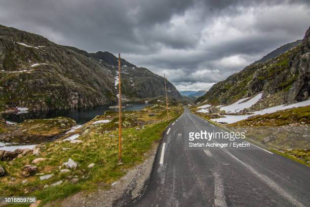 road amidst mountains against sky - hordaland county stock pictures, royalty-free photos & images