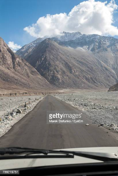 road amidst mountains seen through car windshield - marek stefunko stock photos and pictures