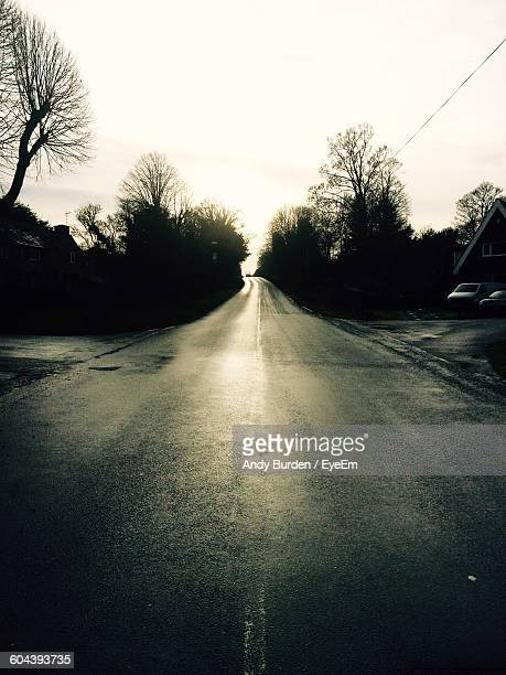 road amidst silhouette trees against sky - malton stock pictures, royalty-free photos & images