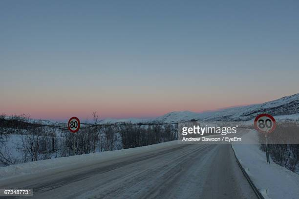 Road Amidst Snow Covered Hills During Sunset