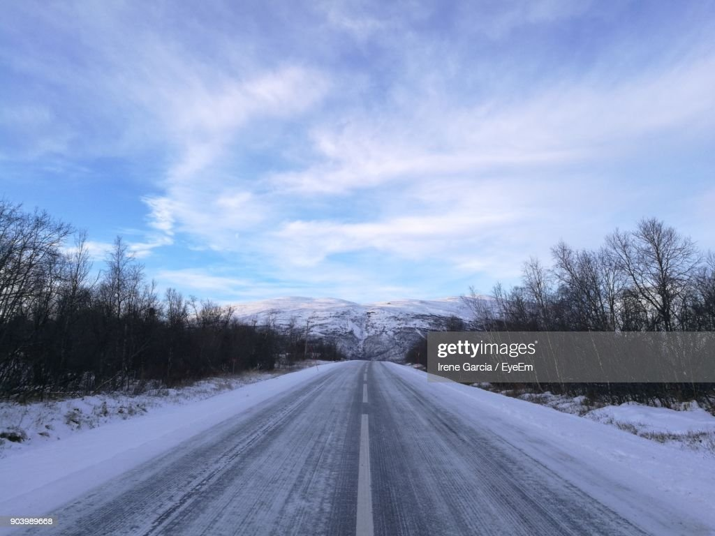 Road Amidst Snow Covered Landscape Against Sky : Photo