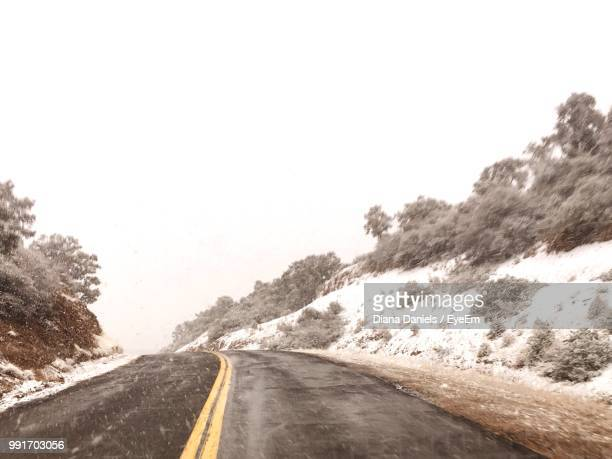 road amidst snow covered landscape against sky - diana daniels stock-fotos und bilder