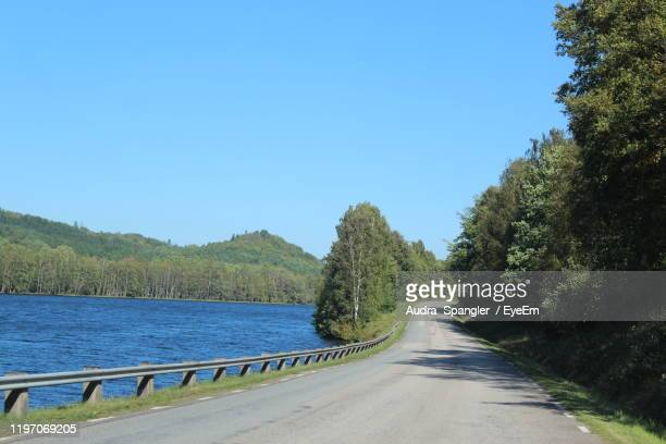 road amidst trees against clear blue sky - vaxjo stock pictures, royalty-free photos & images