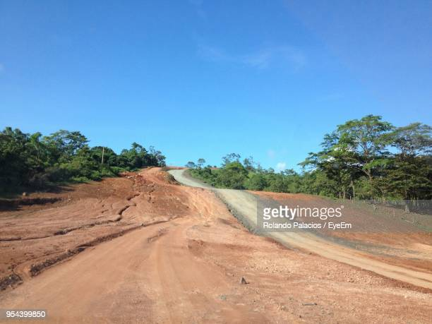 road amidst trees against clear blue sky - central america stock pictures, royalty-free photos & images