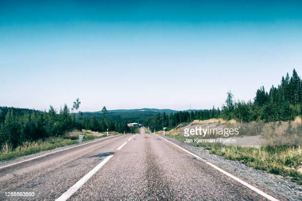 road amidst trees against clear sky - ファールン ストックフォトと画像