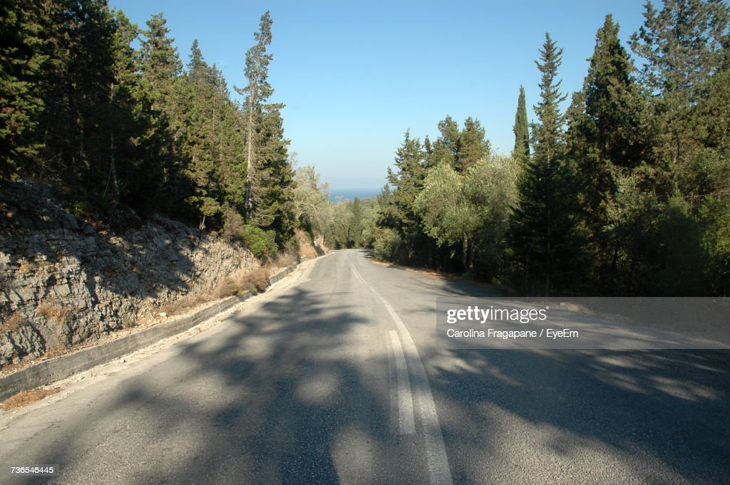 Road Amidst Trees Against Clear Sky : Foto stock