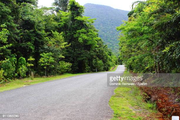Road Amidst Trees Against Mountains