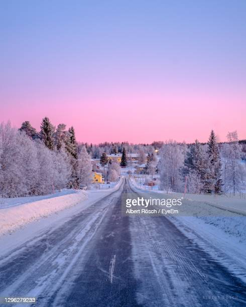 road amidst trees against sky during winter - sweden stock pictures, royalty-free photos & images