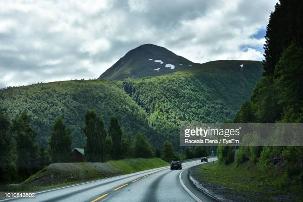 road amidst trees against sky - molde stock photos and pictures