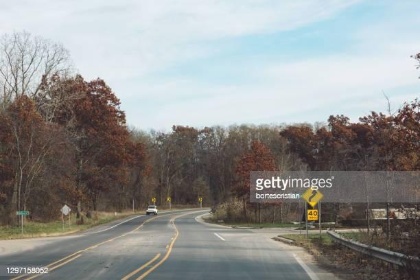 road amidst trees against sky - bortes stockfoto's en -beelden