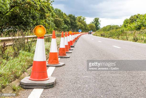 road amidst trees against sky - traffic cone stock pictures, royalty-free photos & images