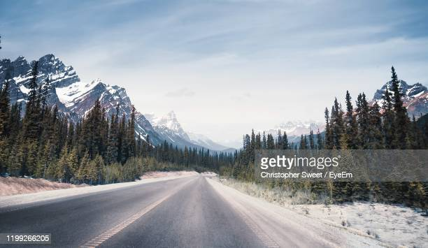 road amidst trees and snowcapped mountains against sky - two lane highway stock pictures, royalty-free photos & images