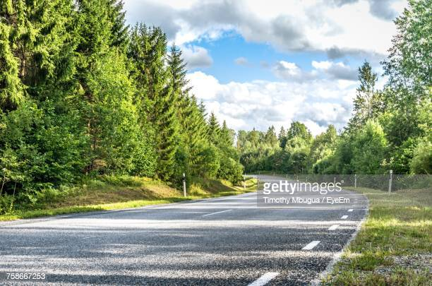 road amidst trees in forest against sky - empty road stock pictures, royalty-free photos & images