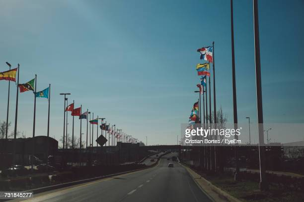 road amidst various flags against sky - bortes stock photos and pictures