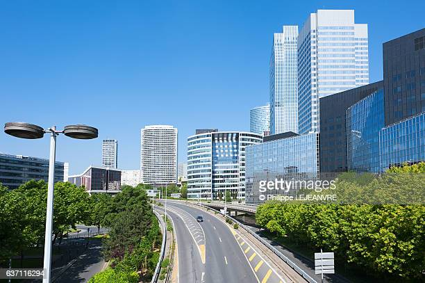 Road and buildings against blue sky in La Defense - Paris financial district