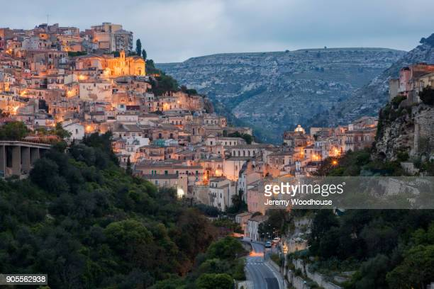 road and cityscape in mountains at night - sicilia foto e immagini stock