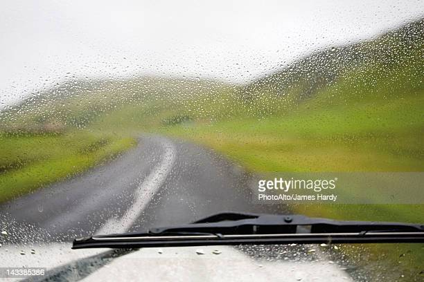 road and countryside viewed through wet car windshield - windshield wiper stock photos and pictures