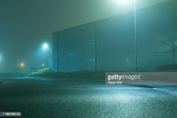 a road and light industrial units, on a foggy, spooky, atmospheric winters night. - fog stock pictures, royalty-free photos & images